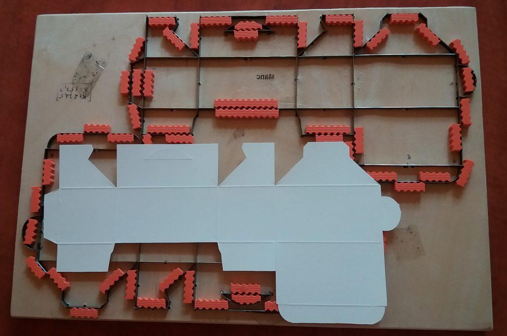 A stancolás bonyolult nyomóformákat is igényelhet. Itt egy névjegydoboz szerszáma  a dobozzal.